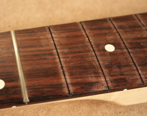 Fretboard with marks after tower pincers